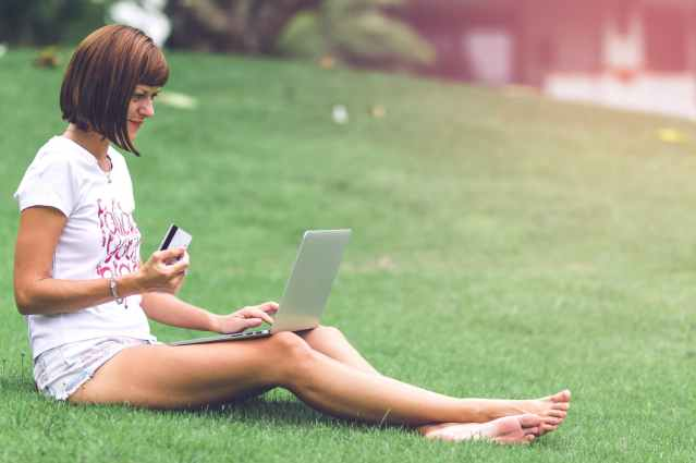woman holding card with macbook air on lap